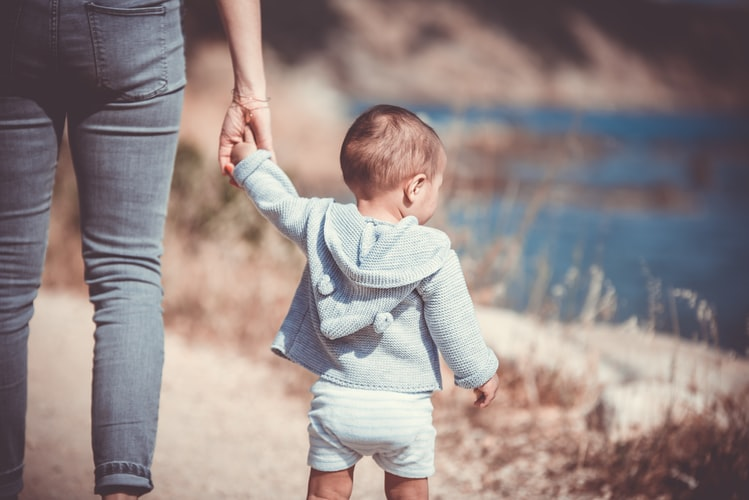 A woman holding the hand of her child outdoors, in a dry environment on a dusty trail, with a pond in the background. The woman and child have their backs facing us.