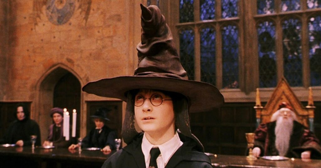 Harry Potter wearing sorting hat, with Dumbledore, Snape, and McGonnagal in the background