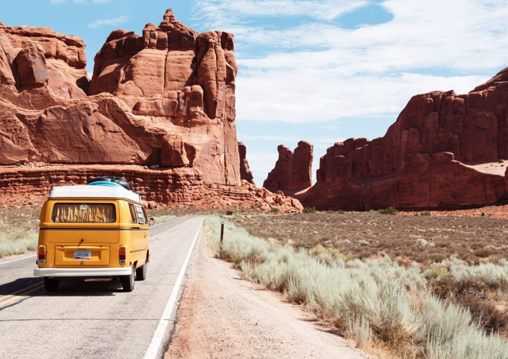 Picture of volkswagon bus in desert with big rocks.