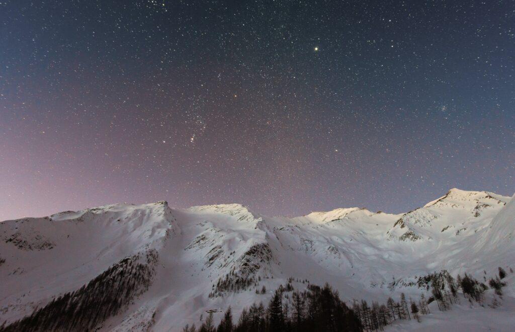 Snowy mountain under starry sky.
