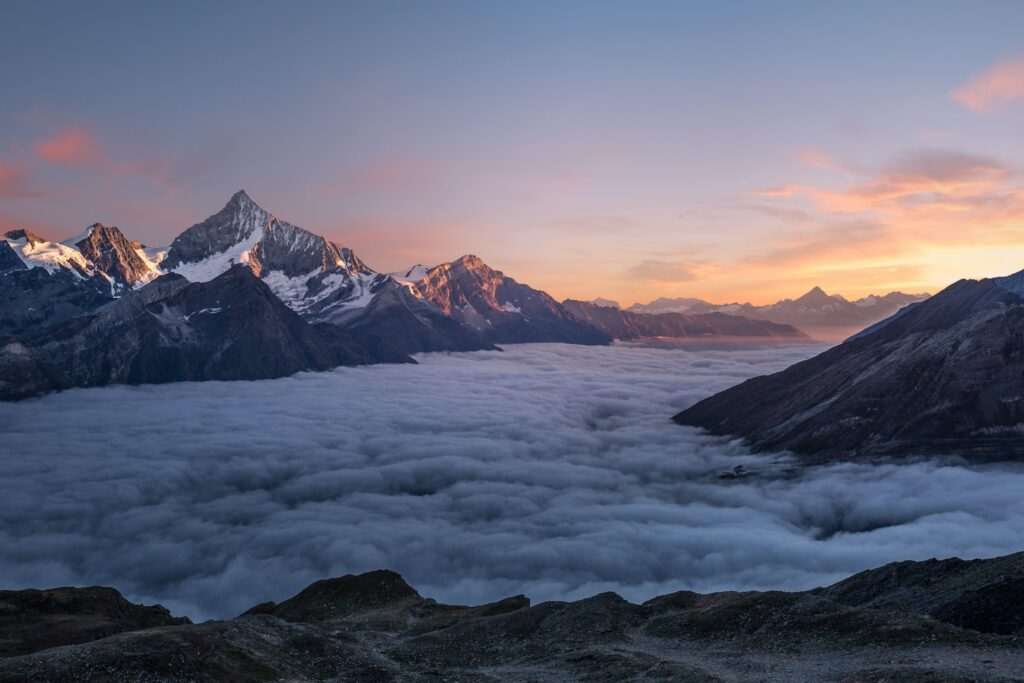 Tops of mountains over clouds with sunset.