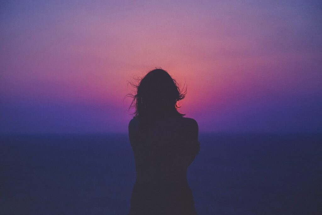Silhouette of girl on purple and red sunset.