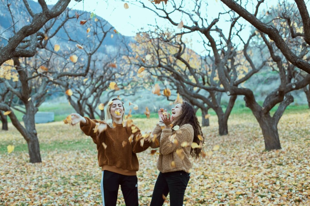 Two girl friends in park throwing yellow and orange leaves in the air in fall. Featuring leafless trees and hills in the background.
